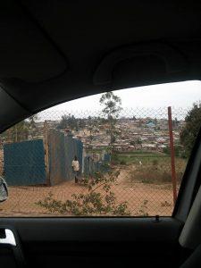 通う子どもたちの車と、そこから遠くに見える小さな家々